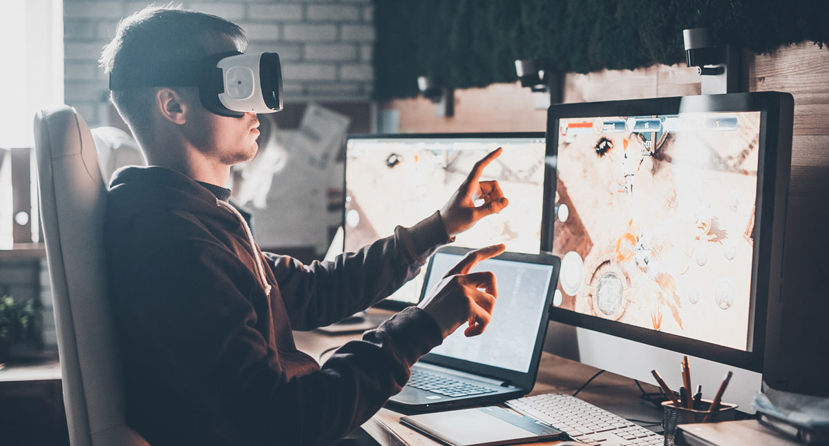 photo of man using VR in front of monitors